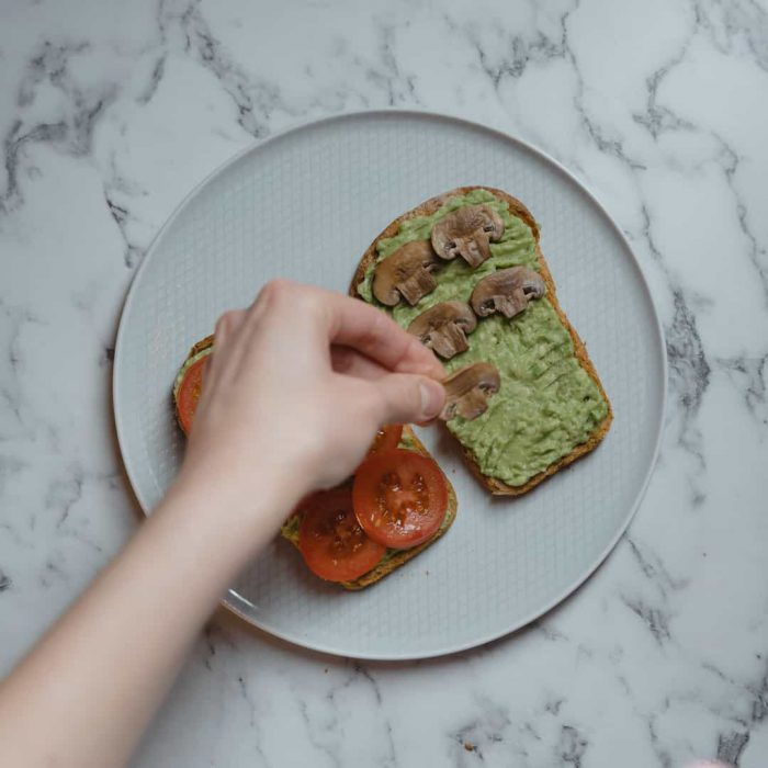 sağlıklı ara öğün hazırlama, el, domates, ekmek, mantar, avokado ezmesi, beyaz tabak, mermer, sunum